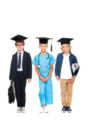 Photo pour Enfants en casquettes de graduation vêtus de costumes de différentes professions debout avec stéthoscope, plan et mallette isolés sur blanc - image libre de droit