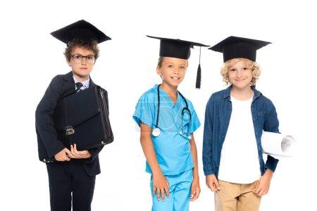Photo pour Enfants en casquettes de graduation vêtus de costumes de différentes professions tenant le plan et la mallette isolés sur blanc - image libre de droit