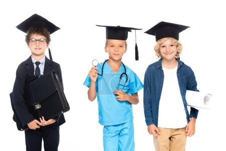 Photo pour Enfants en casquettes de graduation vêtus de costumes de différentes professions tenant le plan, stéthoscope et mallette isolés sur blanc - image libre de droit