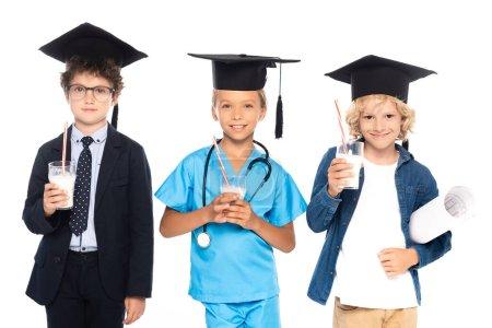 Photo pour Enfants en casquettes de graduation vêtus de costumes de différentes professions tenant des lunettes avec du lait frais isolé sur blanc - image libre de droit