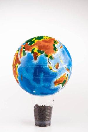 Foto de Globo en copa de plástico con tierra sobre fondo blanco - Imagen libre de derechos