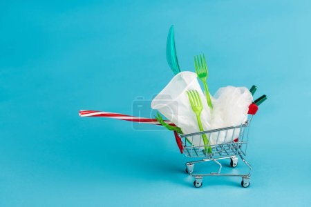 disposable plastic objects in small shopping cart on blue background