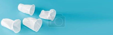 Photo pour Gobelets froissés en plastique jetables sur fond bleu, plan panoramique - image libre de droit
