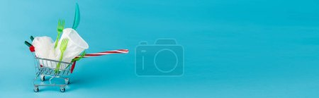 Photo pour Objets jetables en plastique dans un petit panier sur fond bleu, vue panoramique - image libre de droit