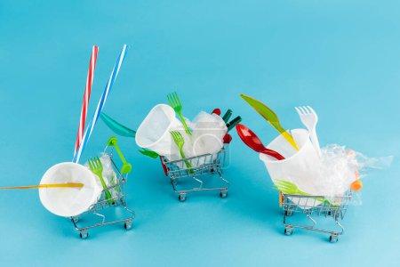 Photo pour Objets jetables en plastique dans de petits chariots sur fond bleu - image libre de droit