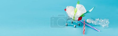 Photo for Disposable plastic objects in small shopping cart on blue background, panoramic shot - Royalty Free Image