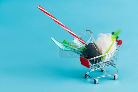 Photo for Disposable plastic objects and ground in small shopping cart on blue background - Royalty Free Image