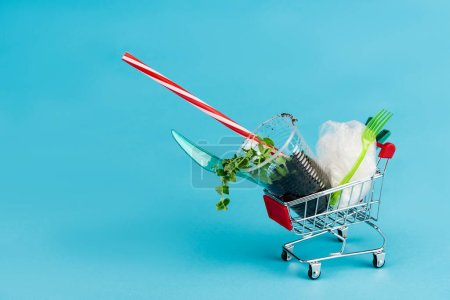disposable plastic objects and plant in ground in small shopping cart on blue background