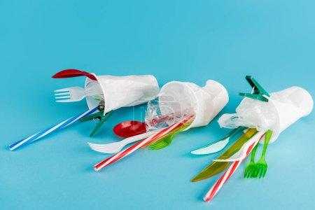 Plastikbecher mit Einwegbesteck auf blauem Hintergrund