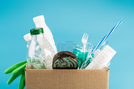 Photo pour Plastic rubbish and rubber gloves in cardboard box isolated on blue - image libre de droit