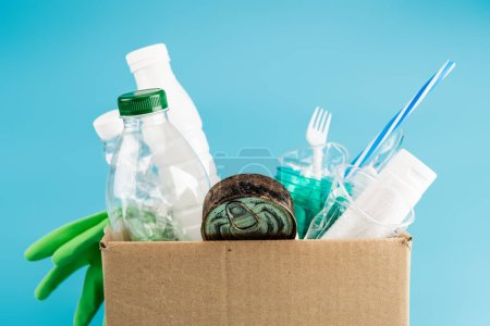 Photo for Plastic rubbish and rubber gloves in cardboard box isolated on blue - Royalty Free Image