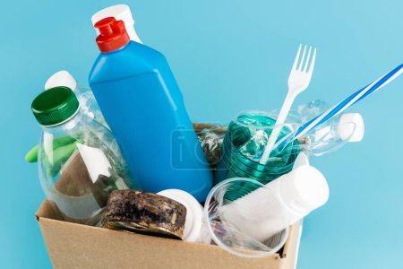 plastic rubbish and rubber gloves in cardboard box on blue background