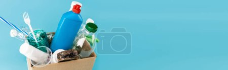 plastic rubbish and rubber gloves in cardboard box on blue background, panoramic shot