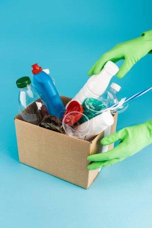 Photo pour Vue recadrée du nettoyant dans des gants en caoutchouc ramassant les déchets dans une boîte en carton sur fond bleu - image libre de droit