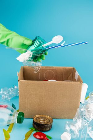 cropped view of cleaner in rubber glove collecting rubbish in cardboard box on blue background