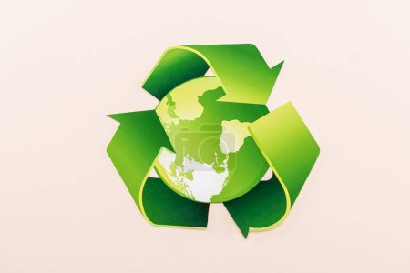 Photo for Top view of green recycling symbol with planet isolated on beige - Royalty Free Image