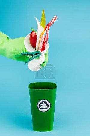 Photo pour Vue recadrée du nettoyant dans un gant en caoutchouc jetant des déchets en plastique dans une poubelle de recyclage sur fond bleu, vue panoramique - image libre de droit