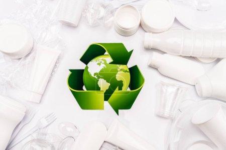 Foto de Vista superior del cartel de reciclaje y basura plástica dispersa sobre fondo blanco - Imagen libre de derechos