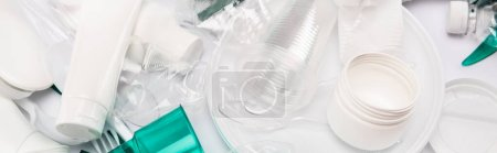 top view of plastic rubbish scattered on white background, panoramic shot