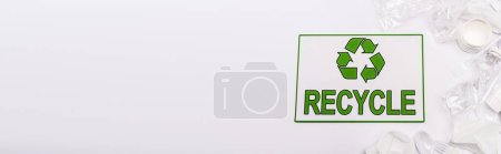 Photo for Top view of recycle card and plastic rubbish scattered on white background, panoramic shot - Royalty Free Image