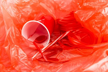 Photo for Red disposable objects on plastic crumpled texture - Royalty Free Image