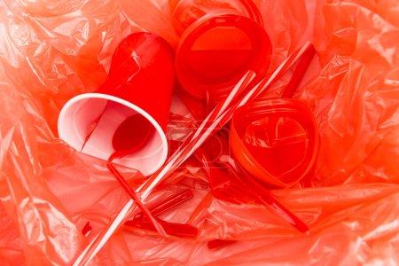 Photo pour Red disposable objects on plastic crumpled texture - image libre de droit