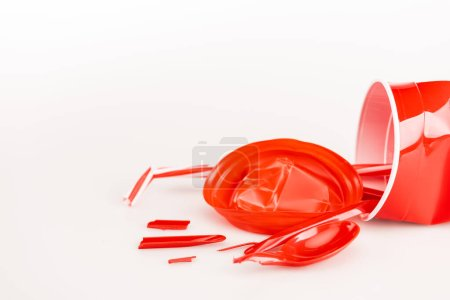 Photo for Broken red plastic objects on white background - Royalty Free Image