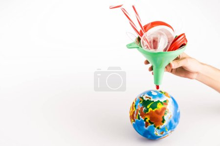 Photo for Cropped view of man holding funnel with plastic above globe on white background - Royalty Free Image
