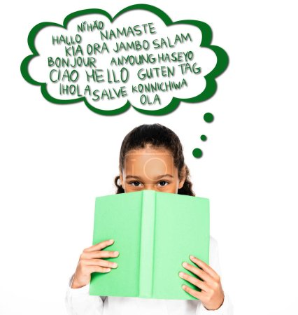 Photo for African american schoolgirl looking at camera while holding book near face isolated on white, illustrated speech bubble with languages - Royalty Free Image
