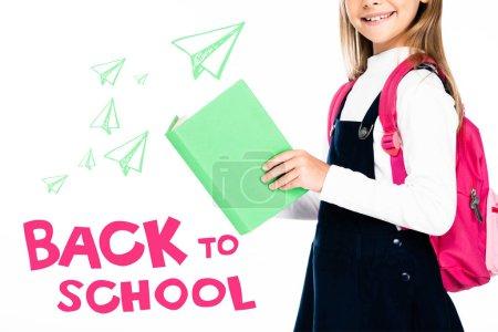Photo pour Vue recadrée de l'écolière tenant le livre isolé sur blanc, illustration de retour à l'école - image libre de droit