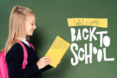 Photo pour Vue de côté du livre de lecture d'écolière près du tableau vert avec illustration bienvenue de retour à l'école - image libre de droit