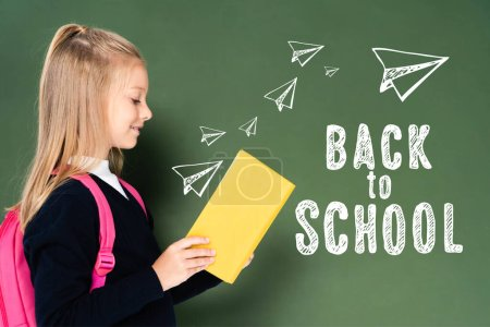 Photo for Side view of schoolgirl reading book near green chalkboard with back to school illustration - Royalty Free Image