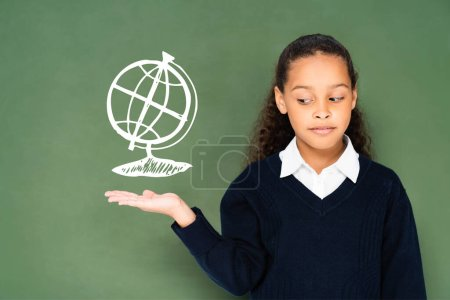 skeptical schoolgirl pointing with hand at globe on green chalkboard