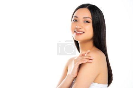 Mujer asiática tocando hombros y mirando a la cámara aislada en blanco