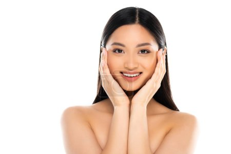 Joyful asian woman looking at camera and touching cheeks isolated on white