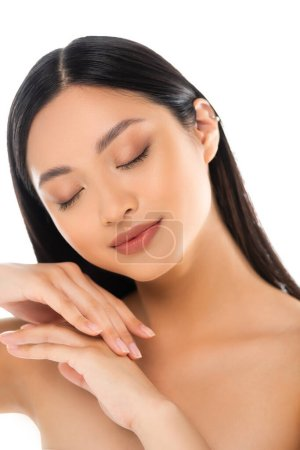 Portrait of young asian woman with closed eyes touching her hands isolated on white