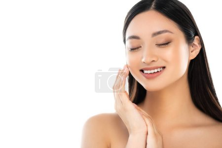 Excited young asian woman with closed eyes touching face isolated on white