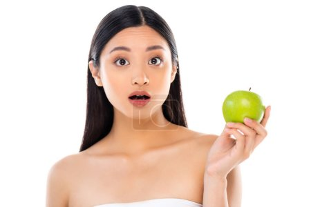 Surprised young asian woman looking at camera and holding apple isolated on white