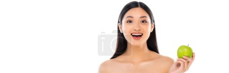 Panoramic shot of excited young asian woman looking at camera and holding apple isolated on white