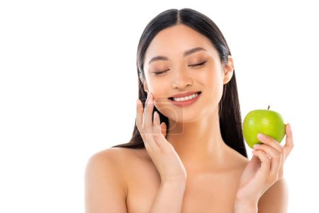 Photo for Excited young asian woman with closed eyes touching face and holding apple isolated on white - Royalty Free Image