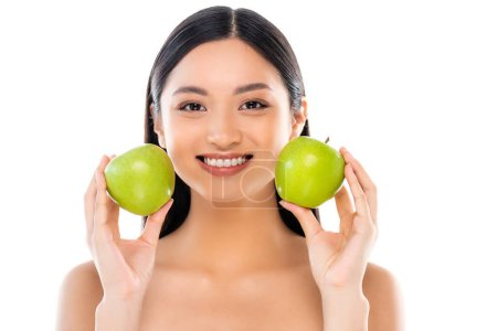 Excited young asian woman holding apples isolated on white