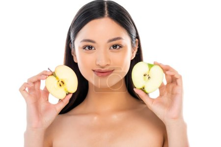 nude asian woman holding halves of ripe apple while looking at camera isolated on white