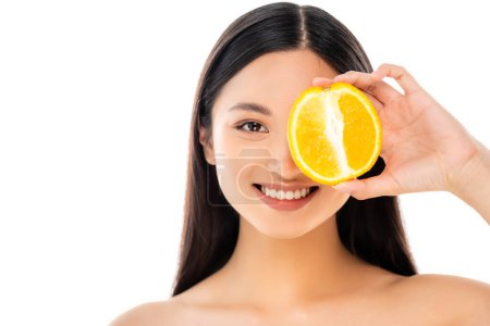 brunette asian woman covering eye with half of ripe orange isolated on white