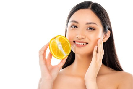 Photo for Nude asian woman touching face while holding half of juicy orange isolated on white - Royalty Free Image