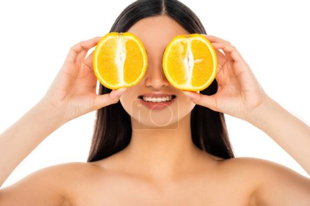 naked brunette woman covering eyes with halves of ripe orange isolated on white
