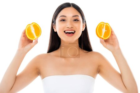 Photo for Excited asian woman looking at camera while holding halves of juicy orange isolated on white - Royalty Free Image