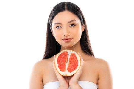 young asian woman looking at camera while holding half of grapefruit isolated on white