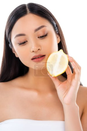 Photo for Dreamy asian woman holding half of juicy lemon isolated on white - Royalty Free Image