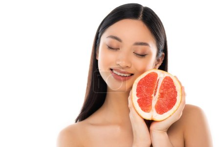 naked asian woman with closed eyes holding half of juicy grapefruit isolated on white