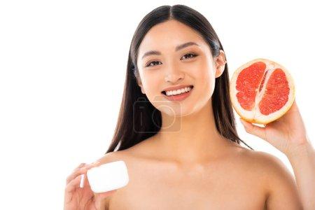 Photo pour Nu asiatique femme tenant la moitié de pamplemousse et de la crème cosmétique tout en regardant caméra isolé sur blanc - image libre de droit